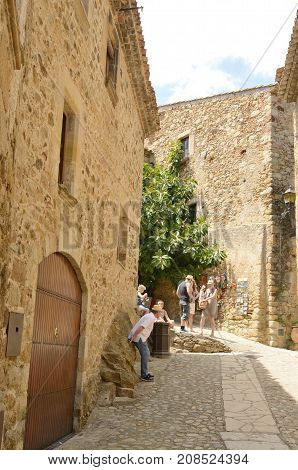 PALS, SPAIN - JULY 25, 2017: People at a narrow alley of the medieval village of Pals located in the middle of the Emporda region of Girona Catalonia Spain.