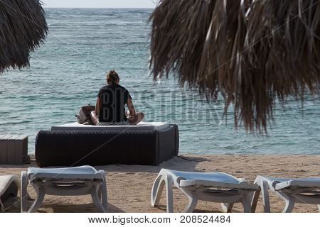 A Young Girl Sit In Front Of The Sea In Yoga Position For Reading A Book On Beach