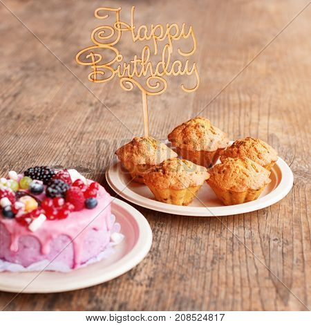 Birthday cake and muffins with wooden greeting sign on rustic background. Wooden sing with letters Happy Birthday and holiday sweets