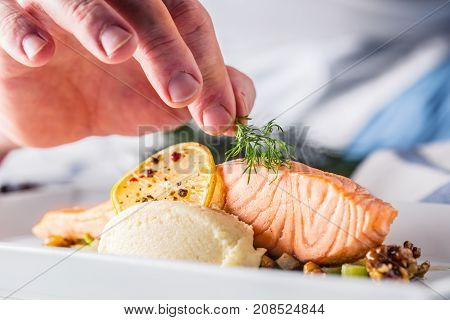 Chef In Hotel Or Restaurant Kitchen Cooking, Only Hands. Prepared Salmon Steak With Dill Decoration