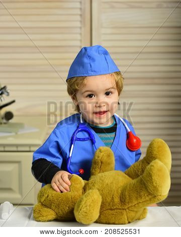 Kid in doctor coat plays with teddy bear. Child with curious face playing doctor. Medical education and childhood concept. Boy in surgical uniform and stethoscope on neck on wooden background