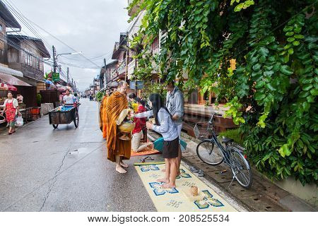 CHIANG KHAN THAILAND - September 10 2016 : Tourists offering sticky rice to Buddhist monk the morning on September 10 2016 at Chiang Khan Loei Thailand.
