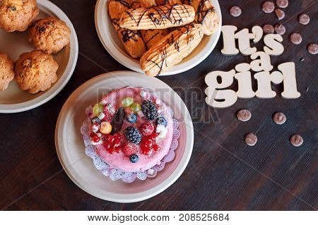 Sweet cheese cake with fresh berries and yoghurt cream and wooden sign Its A Girl. Baby shower party sweets