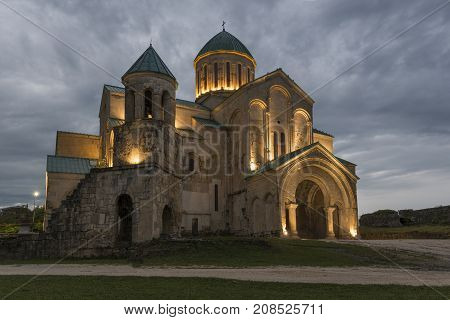 Illuminated Bagrati Cathedral against gray sky background. This ancient church has another names: Cathedral of Dormition or Kutaisi Cathedral.