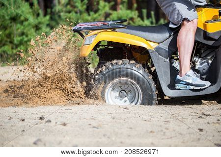 An ATV quadbike get stuck in a sandy road near forest and having wheel-spin making a spray of sand.