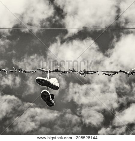 Sneakers hanging on the power line. Blue sky. Bad joke. Black and white photo.