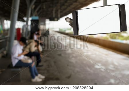 CCTV and LCD TV with white blank screen or billboard copy space for advertising or media and content with people waiting for sky train at station transportation commercial and marketing concept