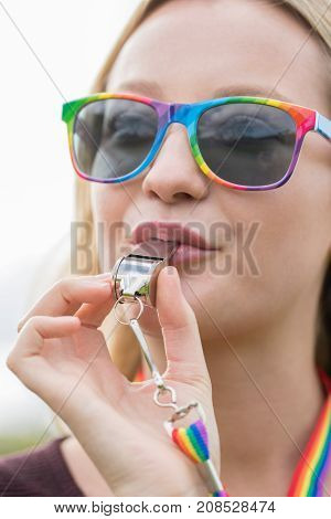 Young Woman Blowing Whistle On Gay Pride Parade