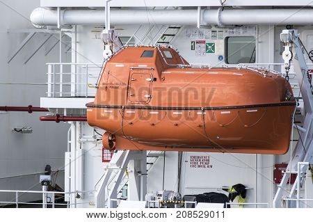 Orange inclosed lifeboat hung from davits an a ship