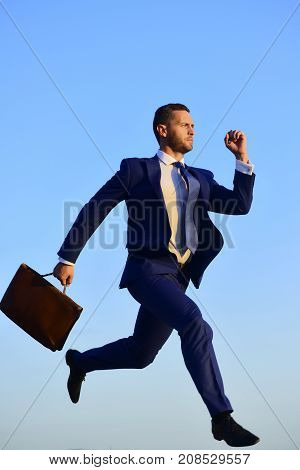 Business and success concept. Businessman makes big step up in air. Man in blue formal suit holds brown case and runs on blue sky background. CEO with concentrated face expression rushes forward