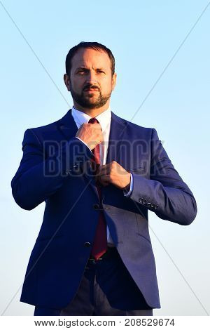 Businessman with beard and confident face expression. Business and leadership concept. Man in formal suit adjusting his red tie. CEO or company leader in blue suit on light blue background
