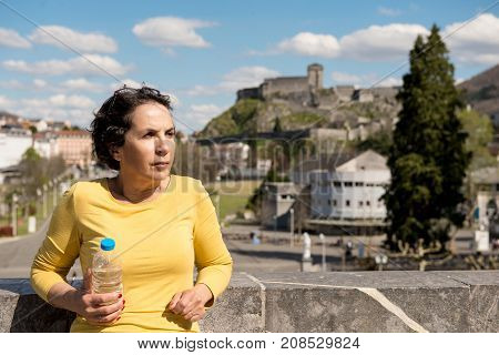 a beautiful brunette woman next to the Basilica of Lourdes