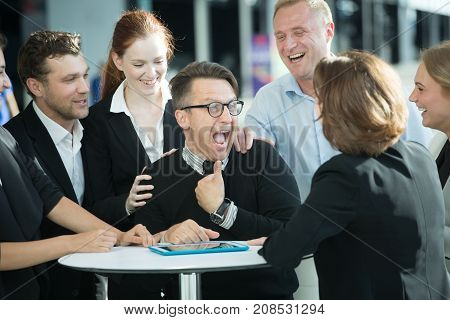 Group of happy business people congratulating their successful coworker