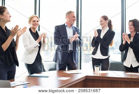 Business people group clapping and smiling in office standing around meeting table