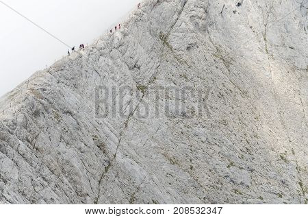 Group of people walking on the edge of Koncheto ridge (Pirin national park, Bulgaria) in extreme weather conditions