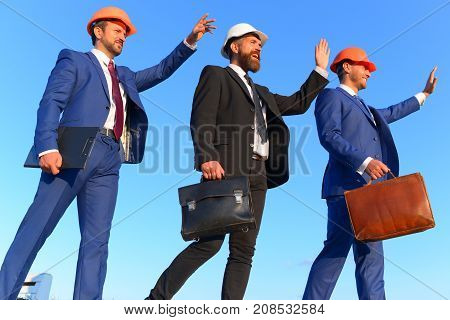 Builders Walk And Wave At Someone On Blue Sky Background.