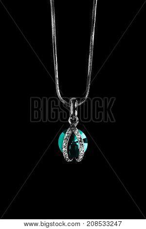 Elegant topaz and diamonds pendant on silver chain on black background