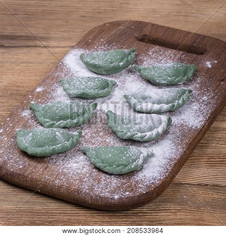 Green crude pelmeni with spirulina. Ukrainian and Russian dishes - vareniki or dumplings with beef meat or mashed potatoes or cottage cheese on a wooden cutting board background close up