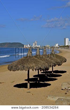 Thatched tiki umbrella on the beach throw their shadow on the fine sand