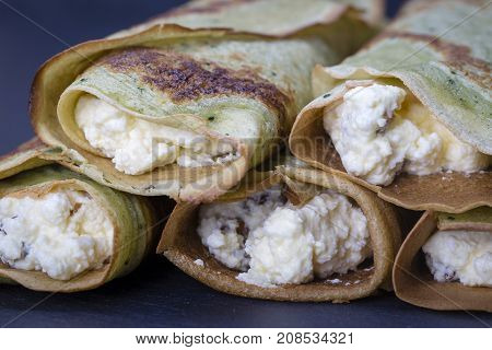 Homemade Pancakes With Green Spirulina Stuffed White Cottage Cheese With Raisins On A Black Slate Ba