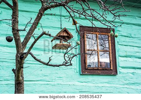 Bird house with feed on the tree in Vlkolinec village Slovak republic Unesco. Green wooden house. Cultural heritage. Travel destination.