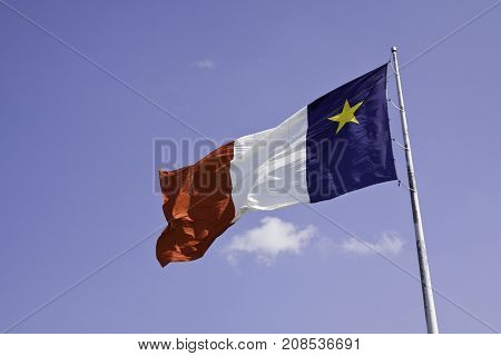 Wide close up of the Acadian Flag of New Brunswick blowing in the wind against a blue sky on a sunny afternoon in August.