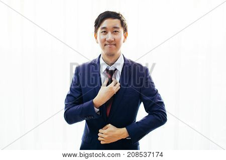 Asian Handsome Man Dressing Up In Formal Suit Over White Background With Copy Space