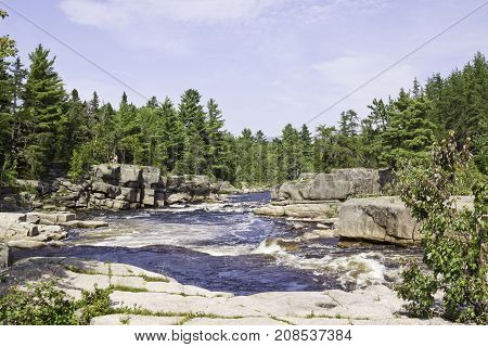 Vertical of rapids running between a rocky shoreline with a rock face in the foreground and surrounded by trees and greenery at Pabineau Falls near Bathurst, New Brunswick on a bright sunny day with blue skies and clouds in August.