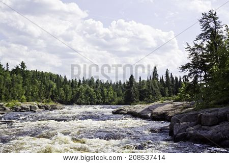 Wide view of rapids running between a rocky shoreline and surrounded by trees and greenery at Pabineau Falls near Bathurst, New Brunswick on a bright sunny day with blue skies and clouds in August.