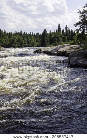 Vertical of rapids running between a rocky shoreline and surrounded by trees and greenery at Pabineau Falls near Bathurst, New Brunswick on a bright sunny day with blue skies and clouds in August.