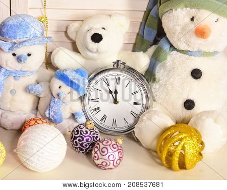 Snowmen teddy bears and Christmas tree balls near oldfashioned alarm clock. Toys placed on wooden wall background. Celebration and New Year decor concept. Winter holiday decorations close up poster