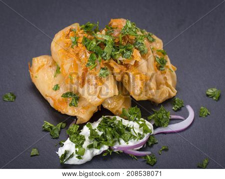 Homemade Stuffed Cabbage Rolls With Rice And Meat In Tomato Sauce On A Black Slate Background, Close