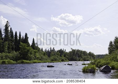 Wide view of a small lake with large rocks on the shoreline and surrounded by trees and greenery at Pabineau Falls near Bathurst, New Brunswick on a bright sunny day with blue skies and clouds in August.