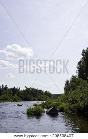 Vertical of a small lake with large rocks on the shoreline and surrounded by trees and greenery at Pabineau Falls near Bathurst, New Brunswick on a bright sunny day with blue skies and clouds in August.