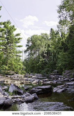 Wide view of a small stream running between boulders and a rocky shoreline surrounded by trees and greenery at Pabineau Falls near Bathurst, New Brunswick on a bright sunny day with blue skies and clouds in August.