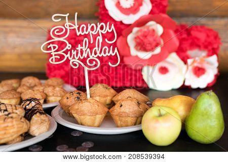 Birthday cakes and muffins with wooden greeting sign on rustic background. Wooden sing with letters Happy Birthday and holiday sweets