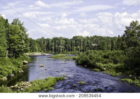 Wide view of a large stream surrounded by trees and greenery at Pabineau Falls near Bathurst, New Brunswick on a bright sunny day with blue skies and clouds in August.