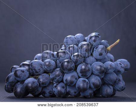 Single Branch Blue Grapes On Black Slate Stone Background