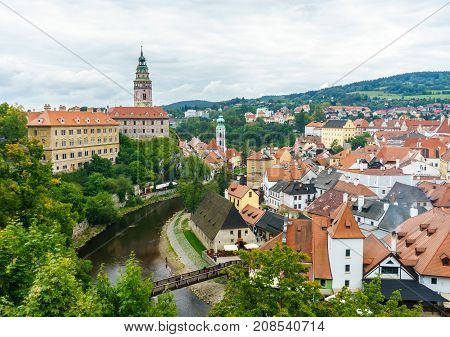 Krumlov Castle and the Czech Krumlov. Medieval fortress and the river Vltava. Red roof tiles and narrow streets. Houses made of stone.