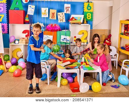 School children with scissors in kids hands cutting paper with teacher in class room. Development and social lerning. Children's project in kindergarten. Boy in the foreground.
