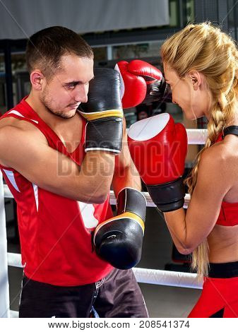 Boxing workout woman in fitness class ring. Sport box exercise two people. Man trainer holding sport mitts in gym. Female box gloves are red backview. loving couple trains together.