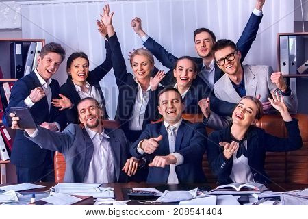 Business people office life of team people are happy with hand up sitting table. Revenue exceeded expenditures for year. People in suits glad with successful deal and celebrate success in office.