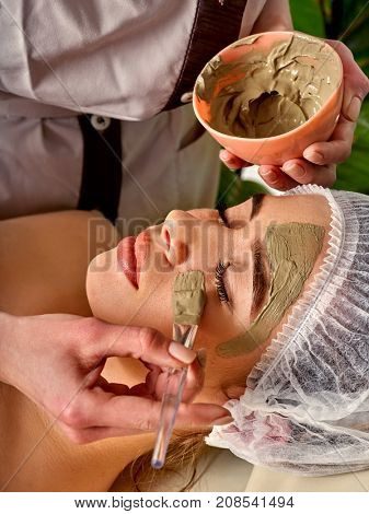 Mud facial mask of woman in spa salon. Massage with clay full face. Girl on with therapy room. Beautician with bowl therapeutic procedure isolated background. Skin softening.