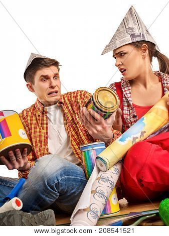 Repair family by happy couple building home. Quarrel family because of renovation in new apartment. Mad woman and man in newspaper cap renovation apartment. Unprofitable loan for repairs.
