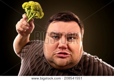 Diet fat man eating healthy food . Health breakfast with vegetables broccoli for overweight person. Male trying to lose weight but he can no longer eat cabbage. Caricature of a fat man.