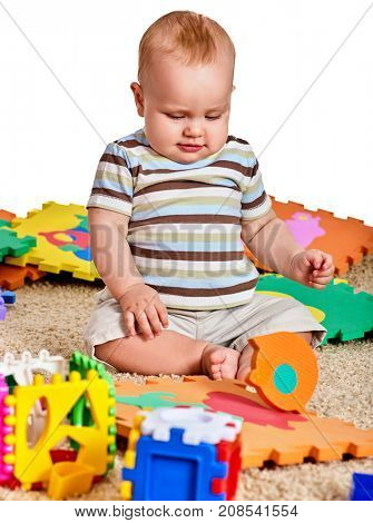 Baby making puzzle. Child jigsaw develops children. Kid holding big pieces and sitting on floor. Portrait of boy playing on soft baby's mat in kindergarten. Logical tasks for development of child.