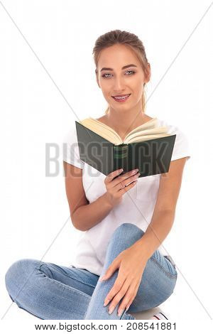 happy young woman reading a novel on white background