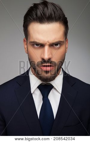 furious young business man looking like a mad man on grey background