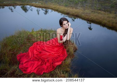 beautiful young woman in fashion red dress posing in a bog