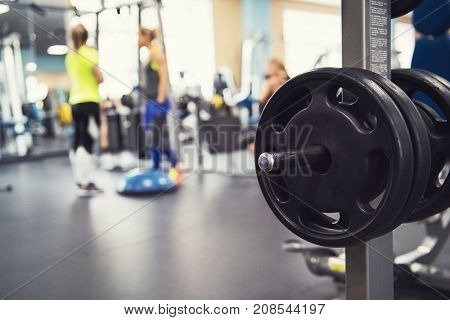 At the fitness modern gym with equipment. Disc weights on the foreground